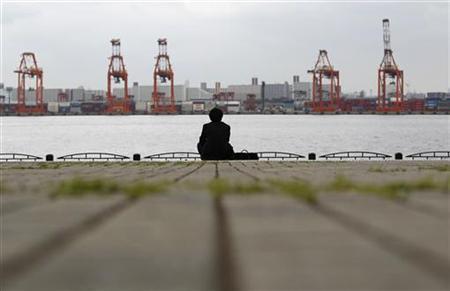 A businessman sits near a cargo area at a port in Tokyo April 19, 2012. REUTERS/Toru Hanai
