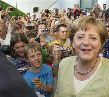 Visitors surround German Chancellor Angela Merkel (R) during open house day at the Chancellery in Berlin, August 19, 2012. REUTERS/Thomas Peter