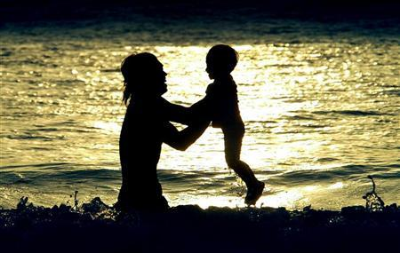 A Balinese father plays with his son on Kuta beach, on the Indonesian resort island of Bali resort on May 10, 2003. REUTERS/Beawiharta