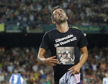 Barcelona's David Villa celebrates his goal against Real Sociedad by wearing a T-shirt with a picture of his family, which reads: ''Impossible without you'', during their Spanish first division soccer match at Nou Camp stadium in Barcelona August 19, 2012. REUTERS/Gustau Nacarino