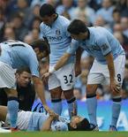 Sérgio Aguero, do Manchester City (abaixo), recebe tratamento após ser lesionado durante uma partida contra o Southampton no Etihad Stadium, no norte da Inglaterra. 19/08/2012 REUTERS/Phil Noble