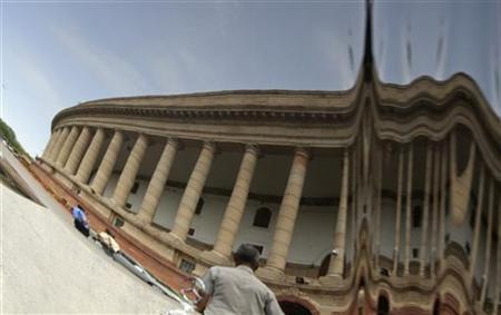 A view of the parliament building is reflected on a car on the opening day of the monsoon session in New Delhi August 1, 2011. REUTERS/B Mathur/Files