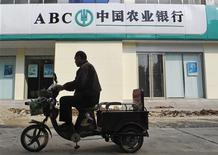 A local rides his motor tricycle past a Agricultural Bank of China branch in Xiangfan, Hubei province, in this October 27, 2010 file picture. REUTERS/Stringer