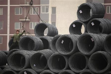 A labourer works on coils of steel wire at a steel wholesale market in Beijing January 17, 2012. REUTERS/Soo Hoo Zheyang