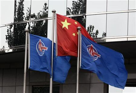 Flags of China National Offshore Oil Corp (CNOOC) fly beside the China flag in front of its headquarters building in Beijing July 25, 2012. REUTERS/Jason Lee
