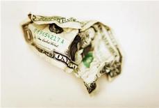 Мятая долларовая купюра в Торонто 22 октября 2008 года. Британский Петропавловск, разрабатывающий золотые месторождения в РФ, сократил чистую прибыль на 90 процентов до $11 миллионов в первой половине 2012 года по сравнению с аналогичным периодом прошлого года из-за роста амортизационных расходов, сообщила компания в четверг. REUTERS/Mark Blinch (CANADA)
