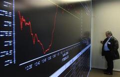 Табло с динамикой котировок в фойе Афинской фондовой биржи, 23 января 2012 года. Европейские акции растут, так как намеки ФРС США на применение новых стимулирующих мер в ближайшее время оказались сильнее волнений по поводу долгового кризиса еврозоны. REUTERS/John Kolesidis