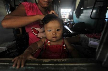 A woman from northeastern states ties the hair of her child while sitting inside the train bound for the Assam state at a railway station in Kolkata August 19, 2012. REUTERS/Rupak De Chowdhuri