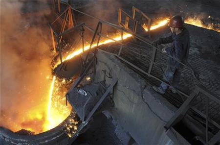 A worker monitors molten iron pouring into a furnace at steel manufacturing plant in Hefei, Anhui province August 15, 2012. REUTERS/Stringer