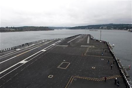 Sailors man the rails on the flight deck of the aircraft carrier USS John C. Stennis as the ship pulls into Bremerton, Washington in this U.S. Navy handout photo dated March 2, 2012. REUTERS/U.S. Navy/Mass Communication Specialist 3rd Class Joshua Keim/Handout