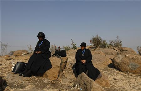 Members from a local church mourn on a hill near a site where miners were killed during clashes at Lonmin's Marikana platinum mine, ahead of a memorial service in Rustenburg, 100 km (62 miles) northwest of Johannesburg, August 23, 2012. REUTERS/Siphiwe Sibeko