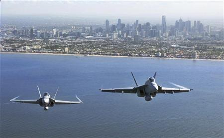 Two Royal Australian Air Force fighter jets, an F/A-18 Hornet (L) and an F/A-18F Super Hornet, fly over Port Philip Bay as part of the Australian International Airshow in Melbourne March 2, 2011. REUTERS/Commonwealth of Australia/Handout