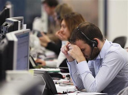 A worker on the IG Group's trading floor looks away from his screens in the City of London, October 4, 2011. REUTERS/Olivia Harris