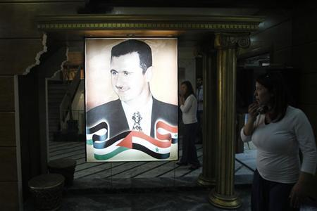 An employee walks near a portrait of Syrian President Bashar al-Assad hanging on the wall inside a Syrian state television and radio building in Damascus August 6, 2012. REUTERS/Khaled al-Hariri