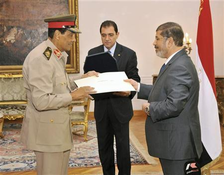 Retired former Egyptian Defence Minister Field Marshal Hussein Tantawi (L) receives a high medal ''The Nile Collar'' from Egyptian President Mohamed Mursi at the Presidential Palace in Cairo August 14, 2012. REUTERS/Egyptian Presidency/Handout