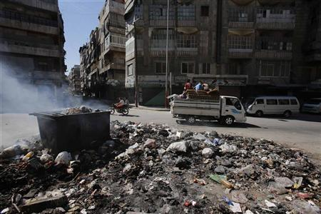 Smoke clears up after residents burn rubbish at the center of Aleppo city, August 23, 2012. REUTERS/Youssef Boudlal