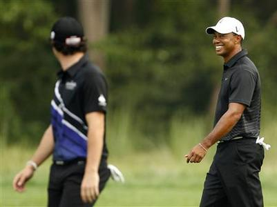 Tiger Woods (R) of the U.S. and Rory McIlory of Northern Ireland talk as they walk up the 13th fairway during the first round of the PGA golf tournament on the Black Course at Bethpage State Park in Farmingdale, New York August 23, 2012. REUTERS/Adam Hunger
