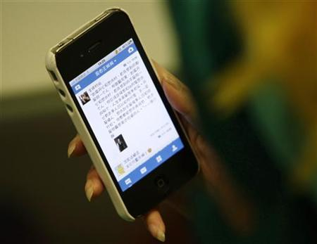 A woman loads a Chinese microblog website on her Apple iPhone in Beijing, September 16, 2011. REUTERS/Jason Lee
