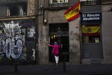 Женщина стоит у входа в здание с испанскими флагами в Мадриде, 13 июня 2012 года. Испания ведет переговоры с партнерами по еврозоне об условиях предоставления ей помощи для снижения стоимости заемных средств, однако страна еще не приняла окончательного решения о запросе, сообщили в четверг источники из еврозоны. REUTERS/Susana Vera