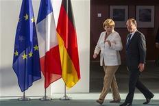 Канцлер Германии Ангела Меркель и президент Франции Франсуа Олланд разговаривают перед брифингом для прессы в Берлине, 23 августа 2012 года. Канцлер Германии Ангела Меркель и президент Франции Франсуа Олланд выступили единым фронтом в четверг, заявив, что Греция не должна ждать поблажек в отношении соглашения о помощи, пока не будет придерживаться заданных ориентиров. REUTERS/Thomas Peter