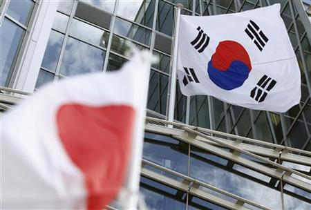 A Japanese flag held by a member of the nationalist movement ''Ganbare Nippon'' flutters under a South Korean flag outside the South Korean embassy, during a protest against South Korean President Lee Myung-bak's visit to a disputed island -- known as Dokdo in Korea and Takeshima in Japan, in Tokyo August 16, 2012. REUTERS/Yuriko Nakao