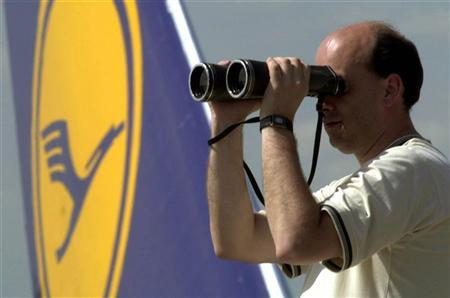 The tail of a Lufthansa plane is seen behind a plane spotter looking through binoculars on the visitor's deck of Frankfurt airport in this May 4, 2001 file photo. REUTERS/Ralph Orlowski