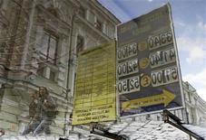 Табличка с курсами валют отражается в московской луже 1 июня 2012 года. Рубль стабилизировался на дневных торгах пятницы после утреннего снижения в ответ на отрицательную динамику нефти и сокращение глобального спроса на риск; сохраняющийся локальный спрос на валюту далее компенсировался предложением валютной выручки под крупные налоги начала следующей недели. REUTERS/Denis Sinyakov