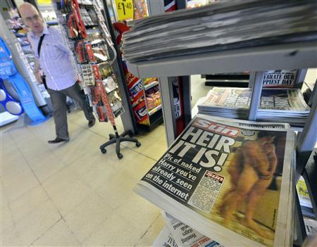 A man passes a newstand displaying copies of The Sun newspaper featuring a picture of a naked Prince Harry in London August 24, 2012. REUTERS/Toby Melville