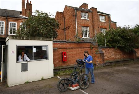 A car park attendant sits in a hut as Clair Graham pushes a ground penetration radar unit during a media event ahead of an archaeological dig in Leicester, central England, August 24, 2012. REUTERS/Darren Staples