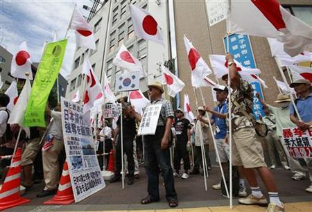 Members of the nationalist movement ''Ganbare Nippon'' holding Japanese national flags take part in a protest against South Korean President Lee Myung-bak's visit to an island -- known as Dokdo in Korea and Takeshima in Japan, near the South Korean embassy in Tokyo August 16, 2012, a day after the 67th anniversary of Japan's surrender in World War II. REUTERS/Yuriko Nakao
