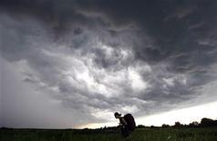 Человек идет под дождевыми облаками на музыкальный фестиваль в Булгаково в 250 км от Москвы, 14 июня 2009 г. Уикенд в российской столице будет прохладным и дождливым, ожидают синоптики.  REUTERS/Denis Sinyakov