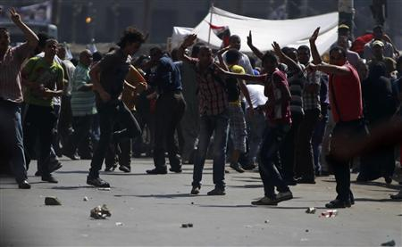 Supporters of Egypt's President Mohamed Mursi take cover from stones during clashes with anti-Mursi protesters in Tahrir Square in Cairo August 24, 2012. REUTERS/Amr Abdallah Dalsh