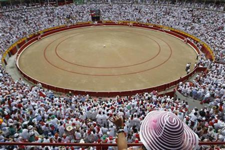 A reveller in a big hat watches a soccer ball thrown to the middle of the bullring at the start of the seventh bullfight of the San Fermin festival in Pamplona July 13, 2012. REUTERS/Susana Vera