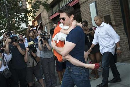 Actor Tom Cruise carries his daughter Suri past a group of photographers as they make their way from a hotel in New York, July 17, 2012. REUTERS/Keith Bedford