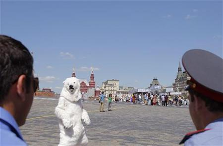 A Greenpeace activist dressed in a polar bear suit looks at Russian policemen during an action on Red Square in Moscow, June 21, 2012. REUTERS/Denis Sinyakov