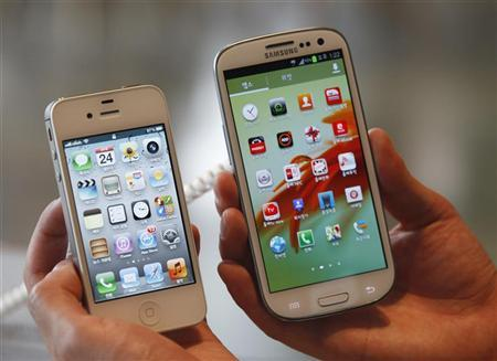 An employee poses as he holds Apple's iPhone 4s (L) and Samsung's Galaxy S III at a store in Seoul August 24, 2012. REUTERS/Lee Jae-Won