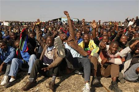 Striking miners hold up their hands as they are addressed by former African National Congress Youth League (ANCYL) President Julius Malema outside a South African mine in Rustenburg, 100 km (62 miles) northwest of Johannesburg August 18, 2012. REUTERS/Siphiwe Sibeko