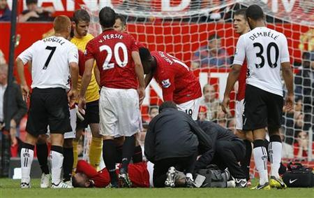 Manchester United's Wayne Rooney (bottom) receives treatment on an injured knee before being stretchered off the pitch during their English Premier League soccer match against Fulham at Old Trafford in Manchester, northern England, August 25, 2012. REUTERS/Phil Noble