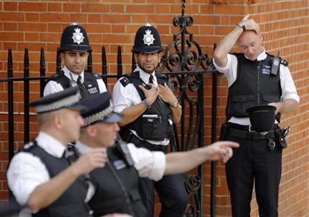 A police officer reacts to the heat of the day before a speech by Wikileaks founder Julian Assange at the Ecuador's embassy, where he is taking refuge in London August 19, 2012. REUTERS/Chris Helgren