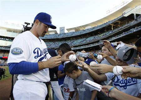 Newly acquired Los Angeles Dodgers first baseman Adrian Gonzalez signs autographs for fans before their MLB baseball game against Miami Marlins in Los Angeles August 25, 2012. REUTERS/Danny Moloshok