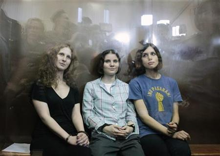 Members of the female punk band ''Pussy Riot'' (R-L) Nadezhda Tolokonnikova, Yekaterina Samutsevich and Maria Alyokhina sit in a glass-walled cage after a court hearing in Moscow, August 17, 2012. REUTERS/Maxim Shemetov
