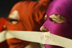 "Activists wear masks with a tape pasted over their mouths in support of members of the female punk band Pussy Riot and during a protest rally in front of the Russian Embassy in Warsaw August 17, 2012. Three women from Russian punk band Pussy Riot were sentenced to two years in jail on Friday for their protest against President Vladimir Putin in a church, an outcome supporters described as the Kremlin leader's ""personal revenge"". The slogan on the tape reads: ""Freedom"". REUTERS/Kacper Pempel (POLAND - Tags: CIVIL UNREST POLITICS)"