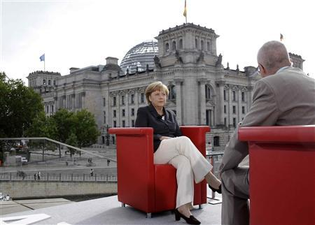 German Chancellor Angela Merkel poses for photographers after the television recording of the ''ARD Sommerinterview'' in Berlin August 26, 2012. REUTERS/Tobias Schwarz