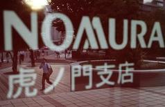 Pedestrians are reflected in a sign displayed outside a Nomura Securities branch in Tokyo June 18, 2012. REUTERS/Issei Kato
