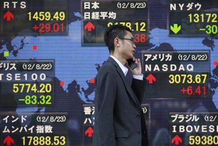 A man passes an electronic board displaying market indices from around the world outside a brokerage in Tokyo August 23, 2012. REUTERS/Yuriko Nakao