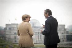 Канцлер Германии Ангела Меркель разговаривает с премьер-министром Греции Антонисом Самарасом (справа) в Берлине 24 августа 2012 года. Канцлер Германии Ангела Меркель в воскресенье попыталась успокоить растущее беспокойство по поводу антикризисной стратегии еврозоны, после того, как Бундесбанк уподобил планы Европейского центробанка на выкуп облигаций опасному лекарству. REUTERS/Bundesregierung/Guido Bergmann