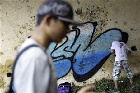 REFILE - ADDING NAME Street artist 9MRO (R), 21, spray-paints graffiti on a wall under a bridge beside a railway line in Yangon August 25, 2012. REUTERS/Soe Zeya Tun