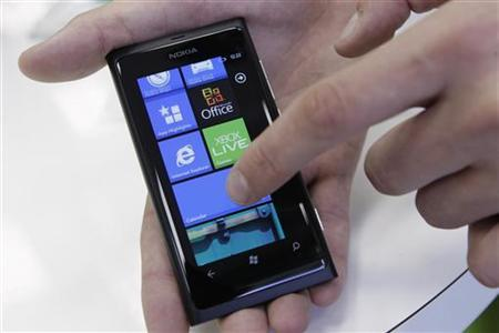 A salesman demonstrates a Nokia smartphone in a shop in Riga July 18, 2012. REUTERS/Ints Kalnins
