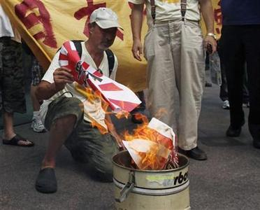 Chief Commander Lo Chau of fishing vessel ''Kai Fung No. 2'', which travelled to the disputed Senkaku, also known as Diaoyu islands, chants slogans with other activists as they burn Japanese military flags outside the Japanese Consulate in Hong Kong August 24, 2012. REUTERS/Bobby Yip