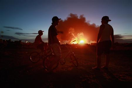 Children watch a fire a day after an explosion at Amuay oil refinery in Punto Fijo in the Peninsula of Paraguana August 26, 2012. REUTERS/Gil Montano